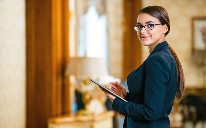 Young business woman wearing suit with glasses using tablet computer at hotel - SIPMM