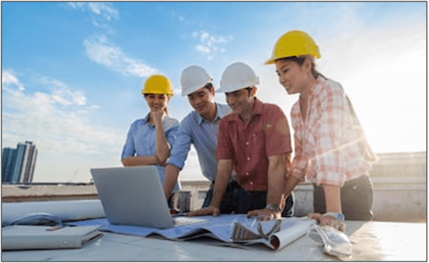 Happy professional construction engineers working with Corporate Colleagues Teamwork and equipment such as blueprint, Safety glasses and technology laptop on the table, Industrial Concept